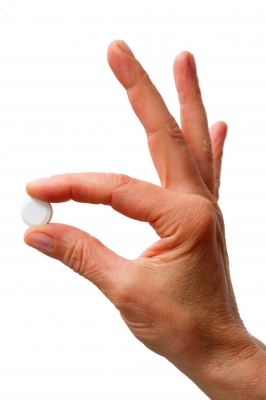 hand holding white pill